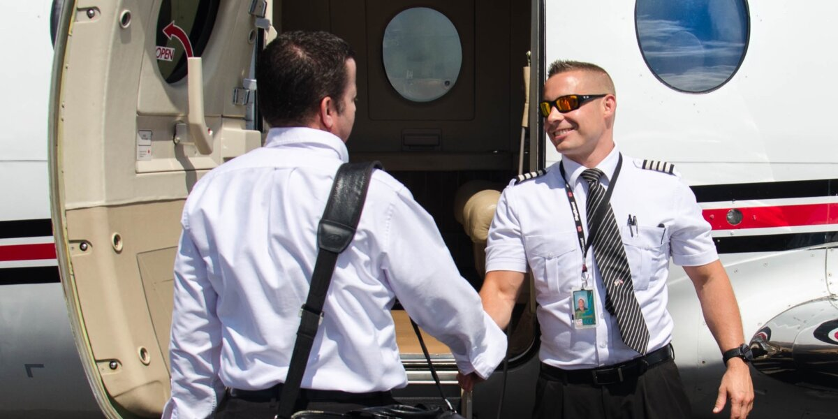 Pilot of a private jet shaking hands with a passenger