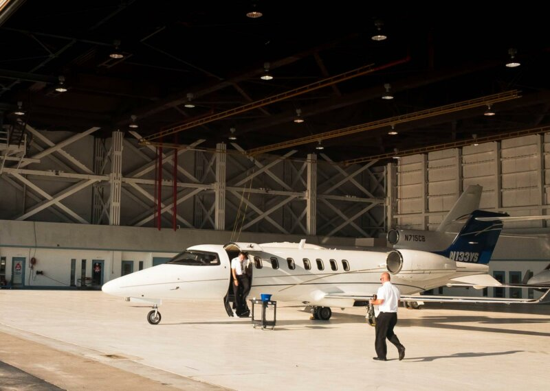 Pilot exiting a private jet in a hangar